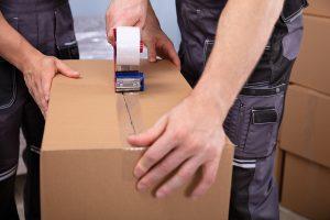 Verhuizers pakken een verhuisdoos in